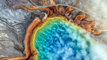 An overhead view of the Grand Prismatic Spring in Yellowstone National Park. Climate change is altering America's first national park so quickly that plants and animals may not be able to adapt.