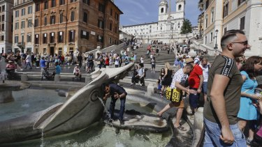 A man takes a selfie while drinking from the Bernini's 17th-century Barcaccia fountain, at the foot of the Spanish Steps in Rome.