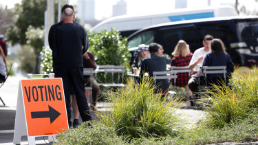 People sit outside at an Auckland cafe near an early voting polling booth on Thursday.