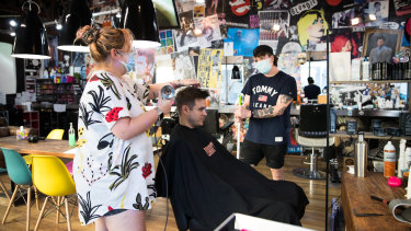 Back open for business: Ziggy Barber Salon's hairdresser Casey Hughes and co-owner Andy Pearson with a client in Surry Hills on Friday.