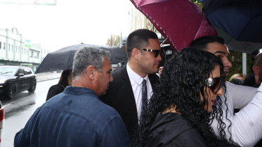 Jarryd Hayne walks into court on Thursday as his supporters attempt to shield him with umbrellas.