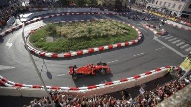 Prancing in the streets: Ferrari driver Kimi Raikkonen during a Formula One cars parade through downtown Milan ahead of Sunday's Italian Grand Prix.