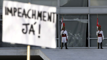"""A sign written in Portuguese that reads """"Impeachment Now!"""" is held during a protest against the Brazilian President's response to the pandemic, in front of the presidential palace in Brasilia on Sunday."""