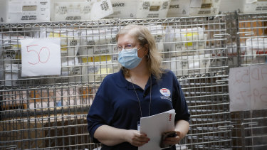 Cages loaded with ballots in postal service bins rest behind a worker at a Board of Elections facility in New York.