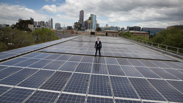 Cr Nick Reece on a roof with solar powered panels.