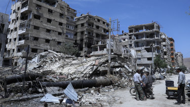 People stand in front of damaged buildings, in the town of Douma, the site of a suspected chemical weapons attack, near Damascus, Syria.