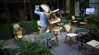 A cafe employee carries chairs as he setting up a terrace in Paris.