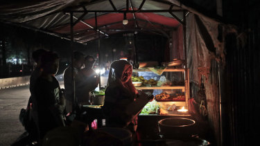A vendor is illuminated by candle light as she serves customers at her stall during a power outage in Jakarta.