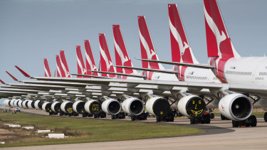Qantas and Jetstar planes grounded at Avalon Airport, with engine covers secured with yellow tape.