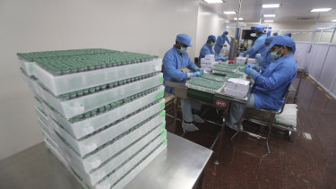 Employees pack boxes containing vials of AstraZeneca's COVID vaccine at the Serum Institute of India, in Pune.