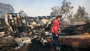 A resident hoses down a shed destroyed by the fire at Bomaderry.