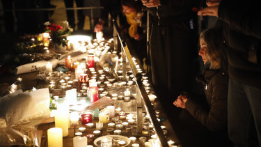 People pay respect and light candles the night following a shooting in Strasbourg, France.