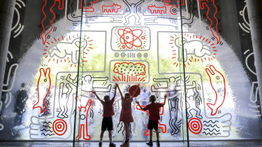 Ferny Creek Primary School students, from left, Archie, Maeve and Reuben check out the recreated mural.