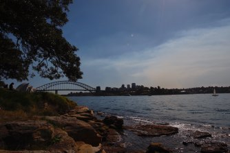 Smoke from Hazard reduction work in northern Sydney drifts across the harbour from Mrs Macquarie's Chair.