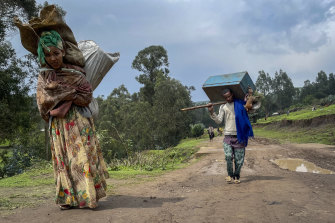 Senait Ambaw, left, who says her home was destroyed in the fighting, carries her belongings out of the town as she looks for a safe place to stay.