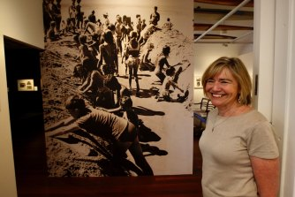 Northern Beaches Council library historian Michelle Richmond with a photo from the library's exhibition showing highlights from the Sydney Morning Herald archives.