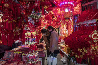 Customers look at red lanterns and decorations at a store at the Yuyuan Bazaar in Shanghai on Wednesday ahead of the Lunar New Year.