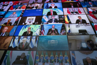 A video monitor shows President Joe Biden, centre, speaking during a virtual Leaders Summit on Climate.