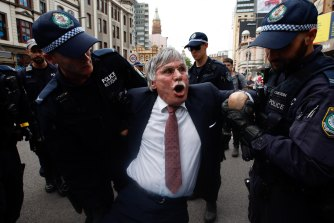 "A man has his wrist bent as he is detained by police during the ""Spring Rebellion"" on October 7 in Sydney."