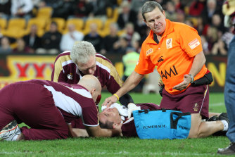 Queensland medical staff attend to Steve Price after he is rocked by Brett White.