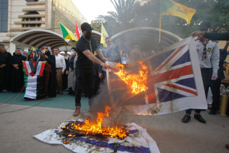 Supporters of the Iran-backed Kataeb Hezbollah militia burn representations of Israeli, US and British flags during a protest in Najaf, Iraq, on September 18, 2020.