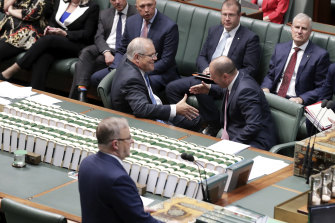 Prime Minister Scott Morrison and Treasurer Josh Frydenberg shake hands after the government's income tax bill passed the House of Representatives in 2019. But the changes will still mean millions of Australians facing bracket creep.
