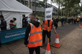 People queue at the Sydney Olympic Park vaccination hub.