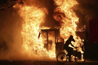 A man on a bike rides past a city truck as it burns outside the Kenosha County Courthouse.