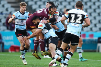 Martin Taupau of the Sea Eagles cops a hit from the Sharks defence.