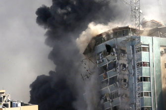 The building housing the offices of The Associated Press and other media in Gaza City collapses after it was hit by an Israeli airstrike.