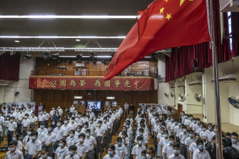 Students stand during a flag-raising ceremony for National Security Education Day at a secondary school in Hong Kong, the first such occasion since the introduction of new national security laws which followed months of pro-democracy protests.