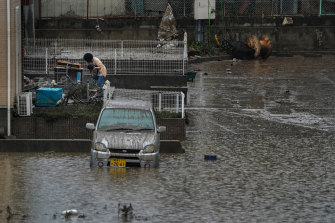 A woman cleans out her home in a still-flooded area in Koriyama, Japan.
