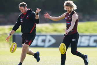 Ben Rutten, left, works with Bombers captain Dyson Heppell at training.