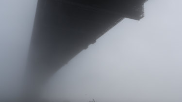 Fog envelopes the Sydney Harbour Bridge.
