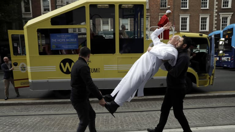 A recently unveiled waxwork of Pope Francis is carried from the National Wax Museum to be put on a refurbished 1979 Popemobile in Dublin, Ireland.