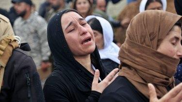 Iraqi Yazidi women mourn during the exhumation of a mass grave in Iraq's north-western region of Sinjar.