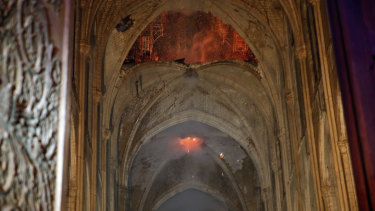 Flames and smoke are seen as the interior at Notre-Dame Cathedral in Paris.