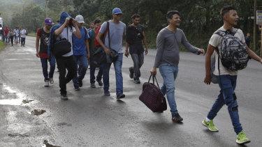 US-bound migrants walk along the roadside as they leave Cofradia, Honduras, on January 15.