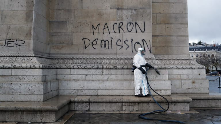 """A worker about to clean graffiti saying """" Macron resignation"""" on the Arc de Triomphe."""