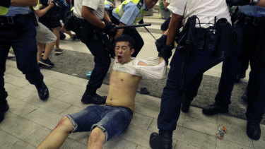 Police drag a protester away.