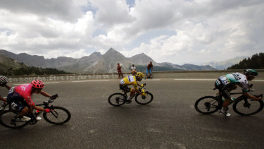 Julian Alaphilippe, wearing the overall leader's yellow jersey, rides with Rigoberto Uran, left, and Gregor Muhlberger, right, during stage 18 of the Tour de France.