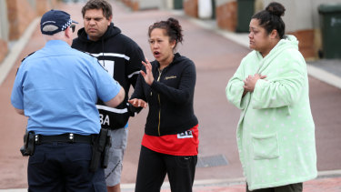 Neighbours speak to police outside the house where  Michelle Petersen and tow of her children were found dead.