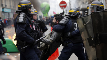 French riot police detain a protester during a rail workers demonstration in Paris,  on Tuesday. French unions plan strikes two days every week through to June.