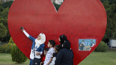 A Syrian girl uses her mobile phone to take a selfie with her family backdropped by a heart shape depicting love for Damascus, at Omayyid Square, Syria, on Tuesday.