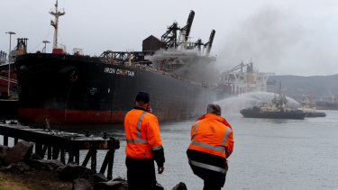 Onlookers watch as tugboats spray water onto the ship in an effort to cool it down.