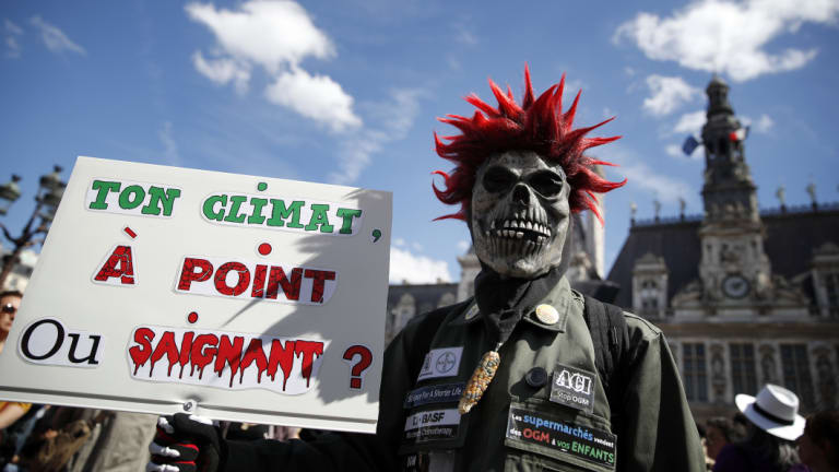 A man holds a poster reading: Your climate. Well done or rare? during a protest, in Paris, on Saturday.