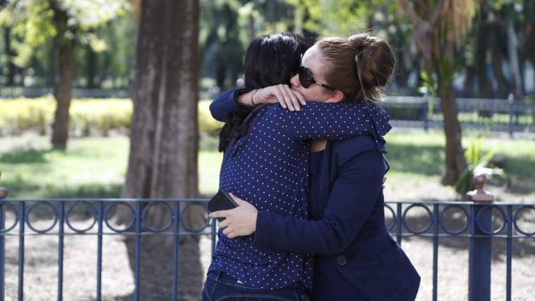 The partner of a member of the crew of a jetliner that crashed in Cuba and another friend, comfort each other in Mexico City, on Friday.