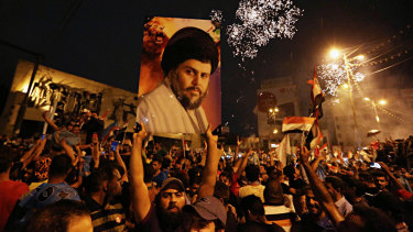 Supporters of Shiite cleric Muqtada al-Sadr, carry his image as they celebrate in Tahrir Square, Baghdad, in May. Poll results are being recounted but a different conclusion is deemed unlikely.
