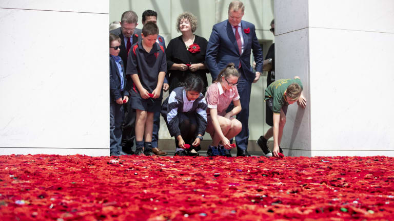 Senator Scott Ryan's son Nick Ryan, Aiden Makem, 10, from Tarcutta Public, Aysha Sajid, 11, from The Grange school in Minto, Annabell Wakefield, 12, from Uranquinty Public near Wagga, and Clay Barton, 11, from Kapooka Public add poppies to the poppy display in the Parliament House forecourt on Friday