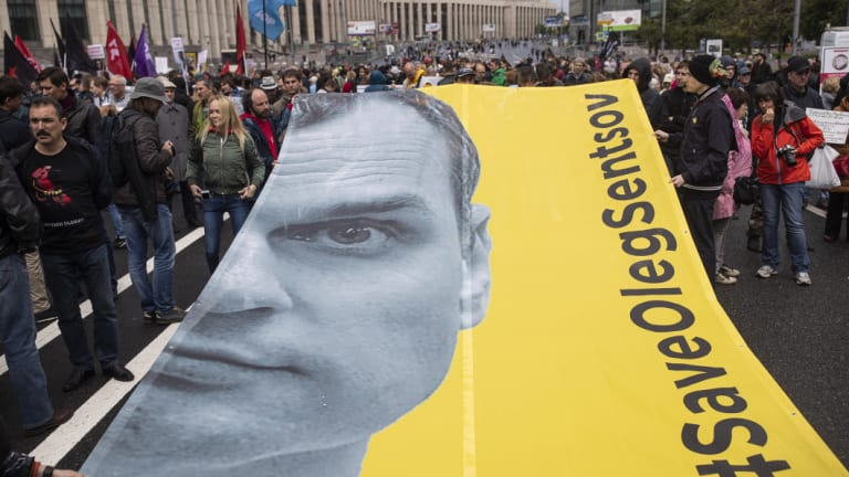 Protesters hold a poster with the image of Oleg Sentsov in Moscow.